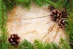 Рамка рождества украшенная с конусами ели и зелеными ветвями Стоковые Фото