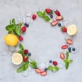 Рамка свежих ягод, мяты и льда на конкретной предпосылке Стоковые Фотографии RF