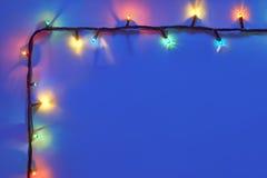 Рамка светов рождества на синей предпосылке Стоковые Фотографии RF