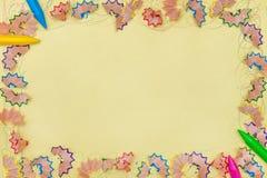 Рамка сделала покрашенных shavings a карандаша на желтой бумаге Стоковое Фото