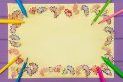 Рамка сделала покрашенных shavings a карандаша на желтой бумаге Стоковое Изображение