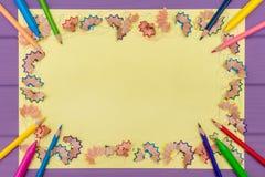 Рамка сделала покрашенных shavings a карандаша на желтой бумаге Стоковые Изображения RF