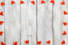 Рамка сделанная красного сердца сформировала конфеты на белой деревянной предпосылке на день валентинки Стоковые Изображения