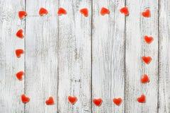 Рамка сделанная красного сердца сформировала конфеты на белой деревянной предпосылке на день валентинки Стоковое Фото