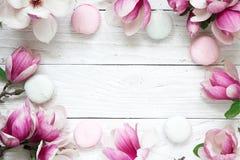 Рамка сделанная розовой магнолии цветет с macarons над белым деревянным столом Насмешка вверх Плоское положение Взгляд сверху Стоковые Изображения RF