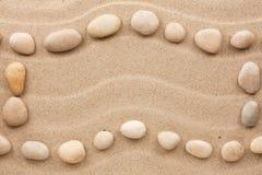 Рамка сделанная белых камней на волнистом песке Стоковые Изображения