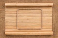 Рамка сделанная веревочки лежа на бамбуковой циновке в форме рукописи Стоковое Изображение