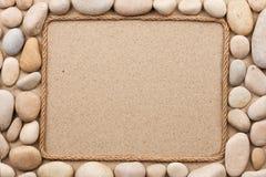 Рамка сделанная веревочки лежа на песке среди белых камней Стоковые Фотографии RF