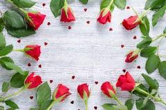 Рамка с 11 красными розами и сердцами, космосом экземпляра на винтажной деревянной предпосылке Стоковое Изображение RF