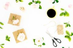 Рамка с цветками роз, подарками, ножницами и mag кофе на белой предпосылке r стоковое фото