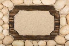 Рамка темной древесины в песке и белых камнях вокруг Стоковые Фото