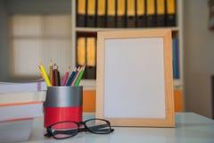 Рамка фото и книга и красочные crayons на таблице в библиотеке Стоковая Фотография