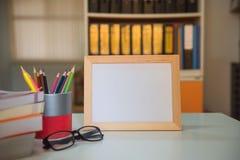 Рамка фото и книга и красочные crayons на таблице в библиотеке Стоковые Фото