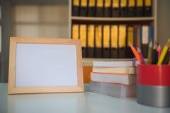 Рамка фото и книга и красочные crayons на таблице в библиотеке Стоковые Изображения RF