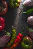 Рамка chili, пестротканых томатов и баклажана на серой таблице Стоковые Изображения