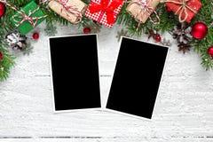 Рамки фото рождества пустые с ветвями, украшениями и подарочными коробками ели над белой деревянной предпосылкой Стоковое фото RF