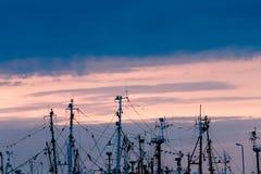 Рангоуты рыбацких лодок в порте с заходом солнца в предпосылке. Стоковая Фотография RF