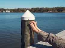 Ноги счастливого ребенка в солнечности на пристани Стоковые Изображения