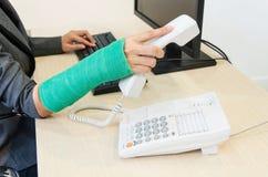 Раненая коммерсантка с зеленым цветом бросила на запястье руки держа telep Стоковое Изображение RF