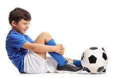 Раненый маленький футболист держа его ногу стоковое изображение
