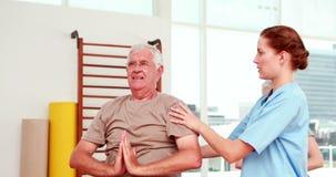 Раненый пожилой гражданин работая с физиотерапевтом акции видеоматериалы