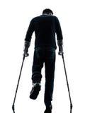 Раненый человек идя с задом силуэта костылей  Стоковая Фотография