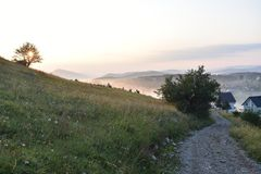 Рано утром, восход солнца и малая дорога деревни гравия и солнце светя через дерево стоковые фотографии rf