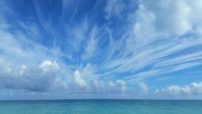 Рано утром на океане: спокойное открытое море с отмелыми пульсациями, в облаках кумулюса голубого неба красивых белых Стоковая Фотография