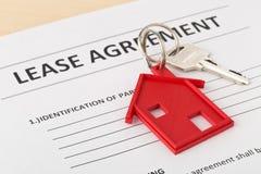 Расквартируйте ключ двери с красным шкентелем ключевой цепи дома и арендуйте agreem Стоковые Фото