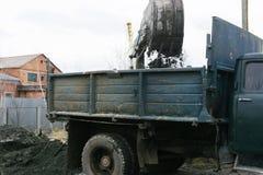 Раскопки и нагрузки старые советские трактора расточительствуют каменный обрабатывать стоковая фотография rf