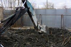 Раскопки и нагрузки старые советские трактора расточительствуют каменный обрабатывать стоковая фотография
