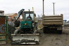 Раскопки и нагрузки старые советские трактора расточительствуют каменный обрабатывать стоковое изображение rf