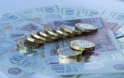 Раскосная линия новых монеток фунта на 10 примечаниях фунта Стоковая Фотография