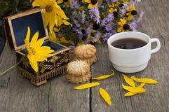 Раскройте ларец, кофе, печенья, лепестки и полевые цветки на старой Стоковые Изображения RF