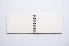 Раскройте белую спиральную тетрадь на белизне стоковое фото