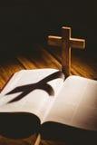 Раскройте библию с значком распятия позади Стоковое Изображение