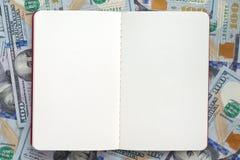 Раскройте блокнот на предпосылке примечаний доллара Стоковое Изображение