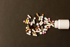 Раскройте бутылку с различными пилюльками на темной предпосылке Взгляд fr стоковое фото