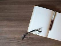 Раскройте блокнот с ручкой и стекла на деревянном столе Стоковые Фотографии RF