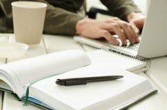 Раскройте блокнот с черной ручкой на работ-таблице Бумажный стаканчик кофе, вещества офиса, компьтер-книжки и деятеля на предпосы стоковое изображение rf