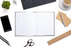 Раскройте дневник окруженный с канцелярские товарами на изолированной белой предпосылке Стоковые Фотографии RF