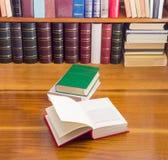 Раскройте книгу и другие книги на деревянном столе и полке Стоковая Фотография