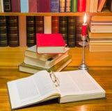 Раскройте книгу и другие книги на таблице светом горящей свечи Стоковые Изображения RF