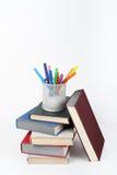 Раскройте книгу, книги hardback красочные на деревянном столе, белой предпосылке задняя школа к Ручки, карандаши, чашка Скопируйт Стоковые Изображения RF