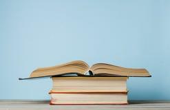 Раскройте книгу, книги hardback на деревянном столе и стену сини Предпосылка образования задняя школа к Скопируйте космос для тек Стоковые Изображения