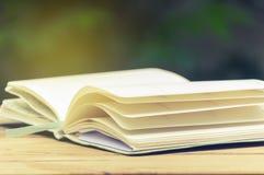 Раскройте книгу на деревянной таблице Стоковая Фотография