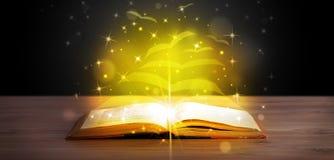 Раскройте книгу с страницами бумаги летания золотого зарева стоковая фотография rf