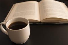 Раскройте книгу с чашкой кофе на черной таблице Стоковое фото RF