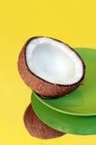 Раскройте кокос на зеленой плите против желтой предпосылки Стоковая Фотография
