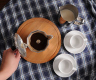 Раскройте кофе гейзера на круглой разделочной доске, кувшина молока и чашки на голубой скатерти шотландки Стоковая Фотография RF